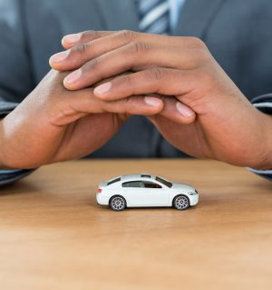 Businessman protecting toy car with hands
